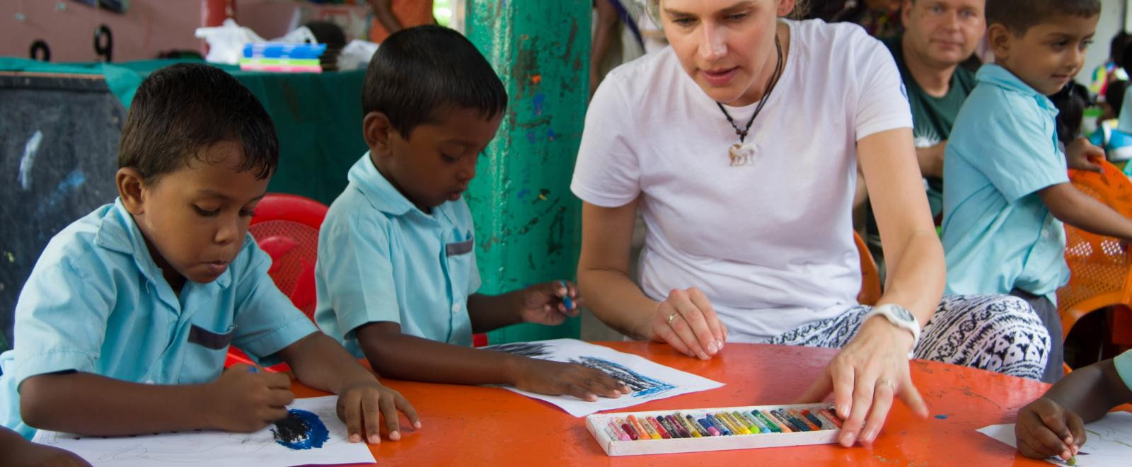 A Polish corporate volunteer works with children in a classroom in Sri Lanka, Asia.